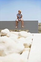Teenage boy sitting at the edge of a terrace (thumbnail)