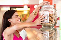 Smiling woman holding a jar of cookies in a bakery