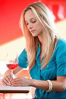 Young woman having red wine and thinking in a bar