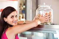 Portrait of a smiling woman holding a jar of cookies in a bakery