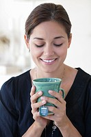 Smiling young woman drinking hot tea at home