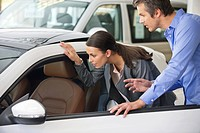 Couple examining a car before buying (thumbnail)