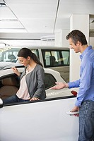 Young woman checking car from inside while man holding the door (thumbnail)