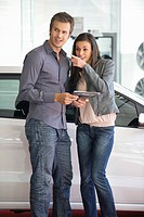 Couple buying a car in showroom