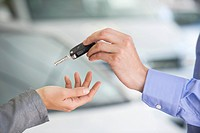 Salesman handing car key to woman