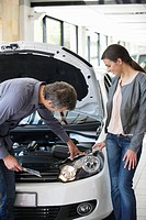 Couple looking at a car engine in a showroom