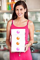 Smiling woman holding cake boxes in a bakery