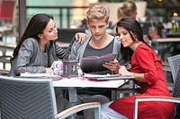 Young man with two young women looking at menu in a restaurant