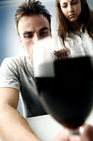 Close_up of a young man holding a glass of red wine