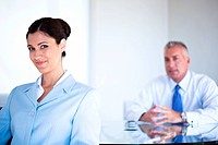 Confident businesswoman in office with businessman in background