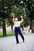 A chinese man enjoy some free time juggling with a handbag in the public park of Temple of Heaven  Beijing  China