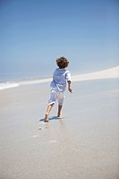 Rear view of a boy running on beach