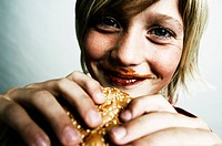 Close_up of a boy holding a burger