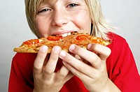 Close_up of a boy biting a pizza
