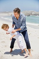 Man playing with his son on the beach (thumbnail)
