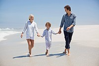 Couple walking on the beach with their son