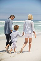 Rear view of a couple walking with their son on the beach