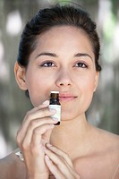 Young woman smelling aromatherapy oil (thumbnail)