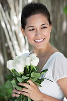 Young woman holding bunch of white flowers and smiling
