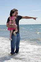 Father holding his daughter and standing in the surf at the lakeshore, Ontario, Canada