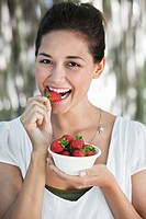 Portrait of a young woman eating strawberry