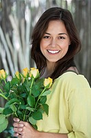 Portrait of a young woman holding bunch of yellow flowers