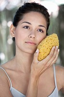 Beautiful young woman holding a bath sponge on her face