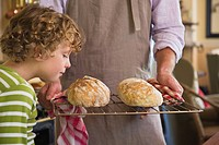 Cute little boy smelling baked bread in father´s hand