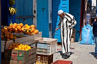 Elderly man entering a fruit and vegetable shop, Essaouira, Morocco