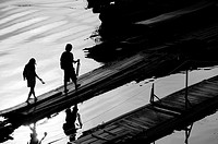 Silhouette of two people, who go over a bridge