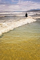 Surfer standing in the surf, Long Beach, Vancouver Island, B.C., Canada