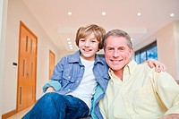 Happy grandfather and grandson embracing on couch