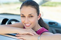 Young woman leaning on car window (thumbnail)