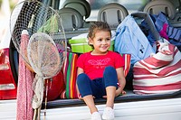 Cute little girl sitting in car trunk