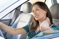 Tired young woman rubbing back of neck while driving a car