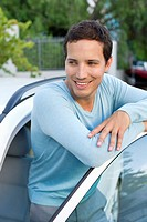 Happy mid adult man leaning at open car door