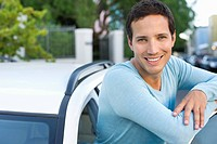 Portrait of a mid adult man leaning at open car door