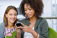 Smiling women using mobile phone in university