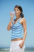 Portrait of a woman drinking water from a water bottle on the beach