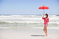 Woman standing on the beach with an umbrella (thumbnail)