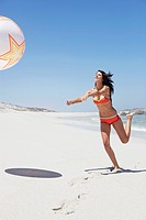 Woman playing with beach ball (thumbnail)