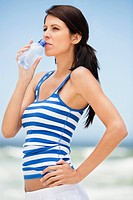Close_up of a woman drinking water from a water bottle on the beach