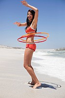 Woman playing with plastic hoops on the beach