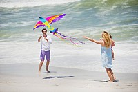Mother carrying child while man flying kite on the beach