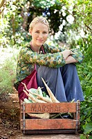 Smiling woman sitting near a crate of vegetables (thumbnail)