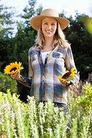 Portrait of a young woman holding sunflowers in a field (thumbnail)