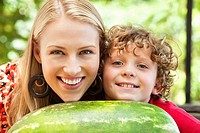 Mother and son leaning on watermelon