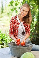 Portrait of a smiling woman washing tomatoes