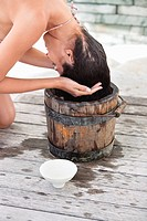 Woman washing hair into a bucket