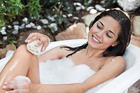 Beautiful young woman taking bubble bath